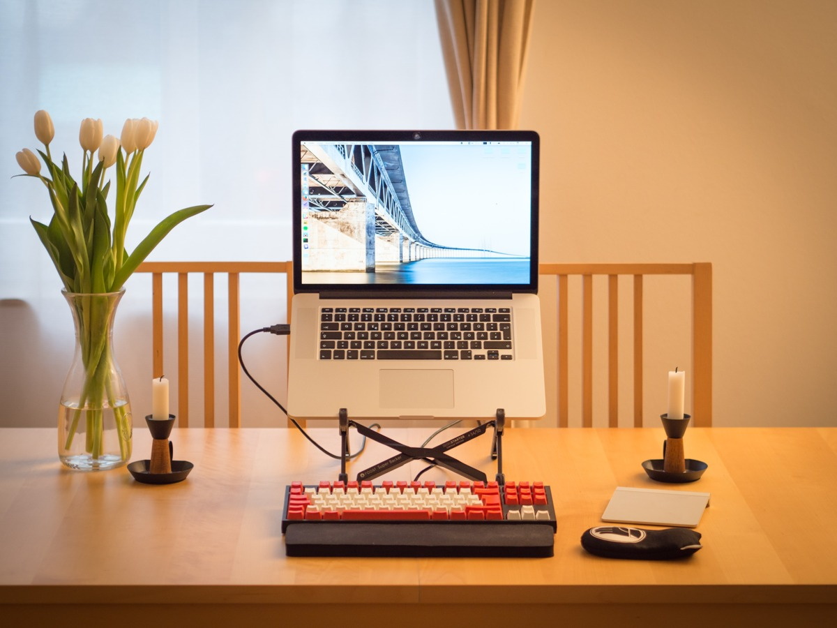 A computer sitting on a desk, a mechanical keyboard in front and two candles to each side.