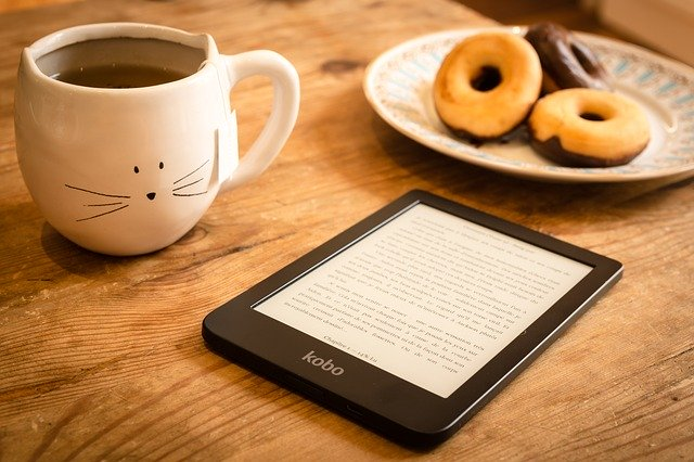 A kobo reader on a table, a cup of coffee and donuts next to it